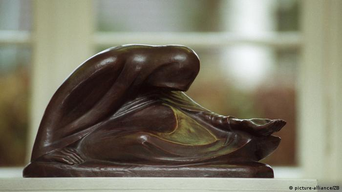 sculpture of a woman on the ground, bent over and with an outstretched hand (picture-alliance/ZB)