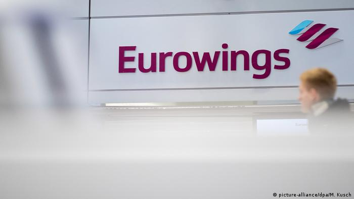A Eurowings employee walks in front of signage at the Dusseldorf airport