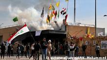 01.01.2020, Irak, Bagdad: Demonstranten stehen mit Fahnen vor Botschaft der Vereinigten Staaten, nachdem sie ein Feuer gelegt haben. An der US-Botschaft im Irak ist es den zweiten Tag in Folge zu Zusammenstößen zwischen Demonstranten und Sicherheitskräften gekommen. Foto: Khalid Mohammed/AP/dpa +++ dpa-Bildfunk +++ |