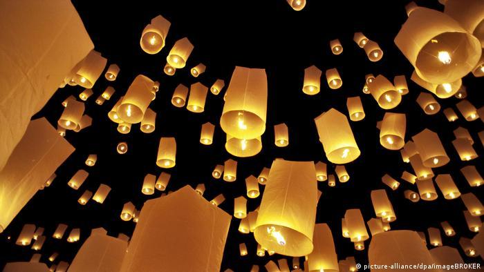 Many sky lanterns rising into the night sky