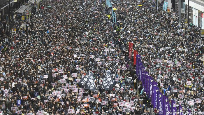 A wide street filled with protesters