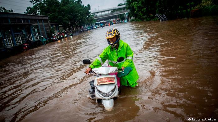 Ein Mann mit einem leuchtend grünen Helm schiebt sein Motorrad durch eine überflutete Straße in Jakarta
