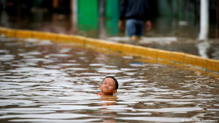 A child swimming in floodwaters