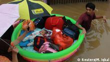 BdT Kinder werden in der Region Tangerang bei Jakarta in einem aufblasbaren Kinderbecken vor der Flut geretet