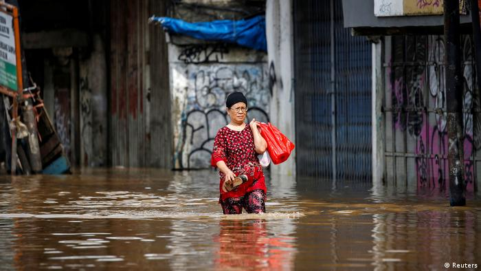 A woman holding a shopping bag wades through floodwaters
