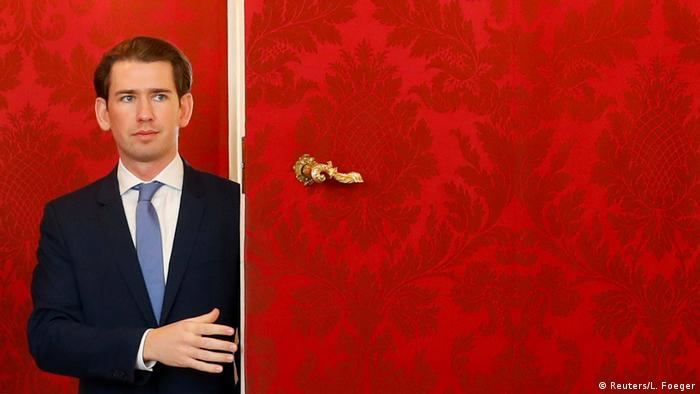 Sebastian Kurz opens a red door at the presidential office in Vienna