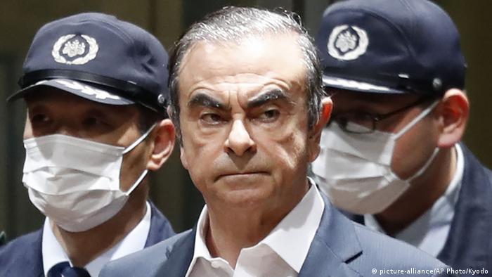 Carlos Ghosn e dois policiais que usam máscaras brancas cobrindo a boca