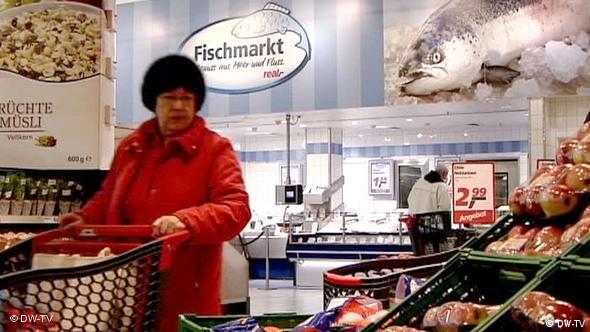 Frau im Supermarkt zwischen verschiedenen Waren (Foto: DW-TV)