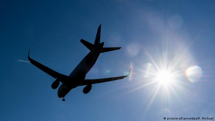 A plane flying with the sun in the background