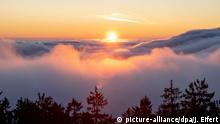 02.01.2020, Schmitten: Blick auf den Sonnenaufgang vom Großen Feldberg im Taunus aus aufgenommen, während dessen Gipfel am Morgen aus einer Hochnebeldecke ragt. Foto: Jan Eifert/dpa +++ dpa-Bildfunk +++   Verwendung weltweit