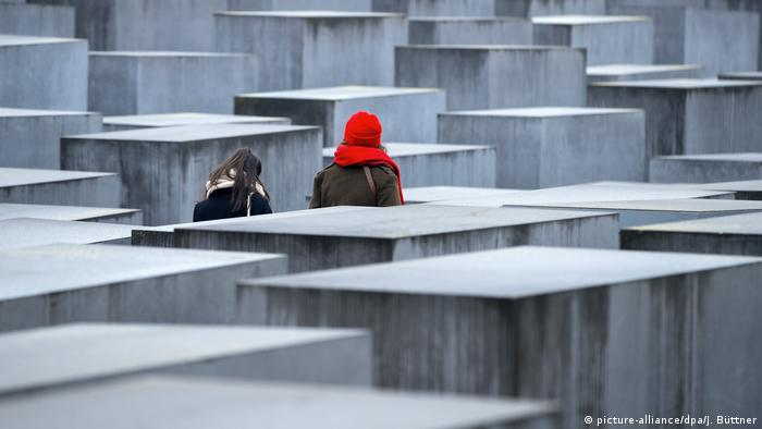 People walking among the pillars of the Memorial to the Murdered Jews of Europe in Berlin (picture-alliance/dpa/J. Büttner)