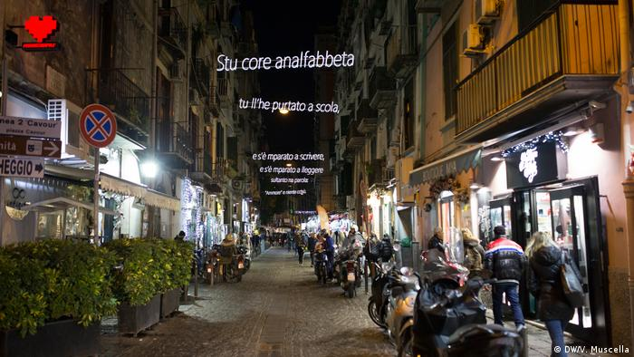 The verses of a poem by Neapolitan actor Antonio De Curtis, also known as Toto, illuminate a street in Rione Sanita, Naples