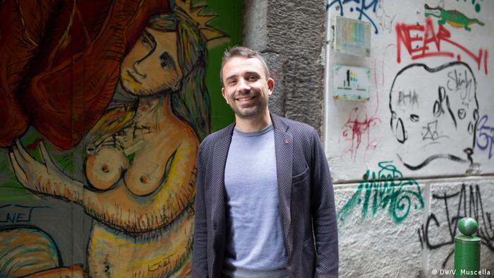 Antonello Sonnino poses for a portrait in front of graffiti on a Naples street