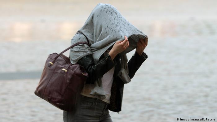 Foto de una persona tapándose de la lluvia