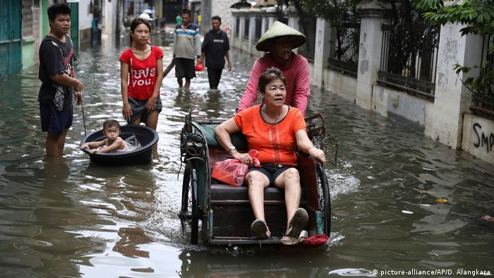 A woman is pushed down a flooded street in Jakarta, Indonesia. (picture-alliance/AP/D. Alangkara)
