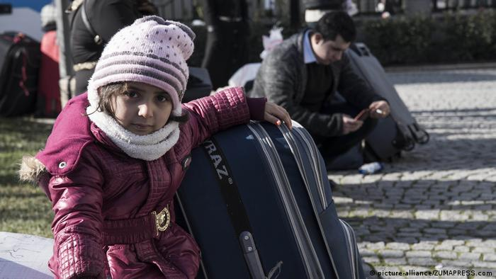 A Syrian child holds a suitcase as she and her family wait to be transported to Syria in January 2019