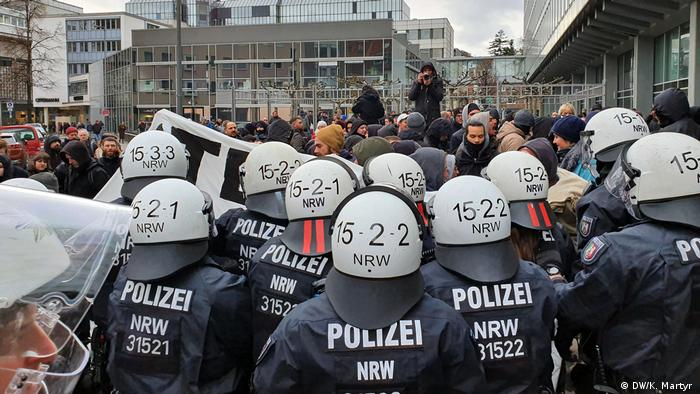 Demonstrators face police officers in front of the WDR building in Cologne (DW/K. Martyr)
