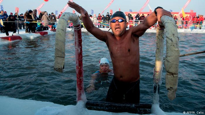 Swimmer getting out of the water, obviously feeling cold (AFP/N. Celis)
