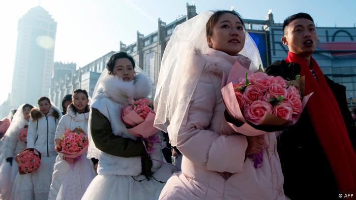Couples, dressed in warm coats, lining up for a mass wedding at the Harbin festival (AFP)