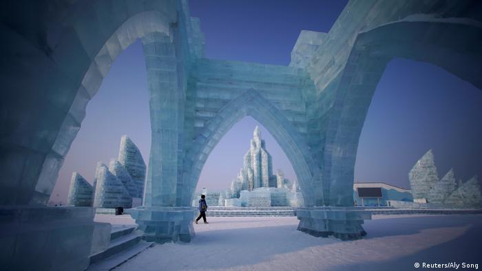 A woman walking past ice sculptures Harbin Ice & Snow Festival (Reuters/Aly Song)