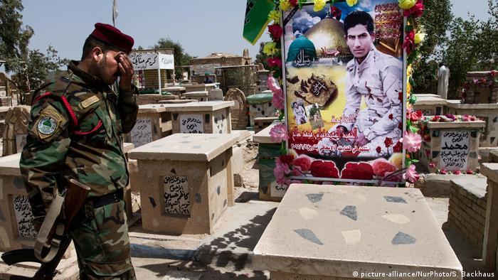 Irak Najaf | Kämpfer der Ali Al-Kataib Brigade am Grab eines verstorbenen Kameraden (picture-alliance/NurPhoto/S. Backhaus)