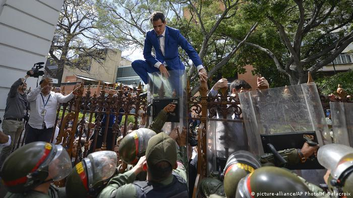 Juan Guaido jumps over a fence