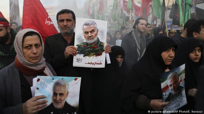 Pessoas vestidas de preto empunham fotos de general iraniano Qassim Soleimani
