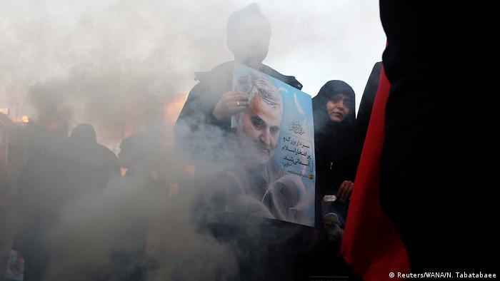 Mourners for Soleimani walk through smoke in Tehran
