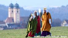 Carol singers dressed as the Three Kings in Germany with church in background (picture-alliance/dpa/P. Seeger)