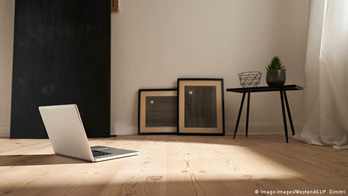Laptop sits on floor of bare room with only a few other objects