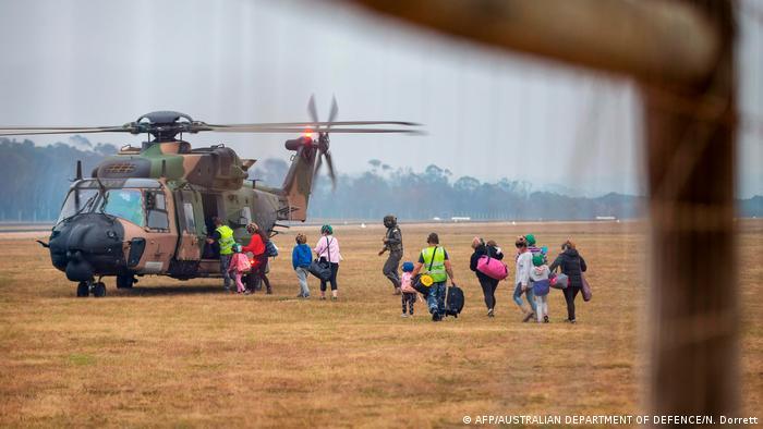 Pessoas correndo para embarcar em helicóptero