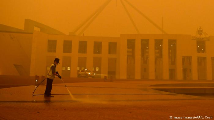 The man in front of the Australian Parliament in Canberra failed to cover the flames with his high-pressure cleaner.