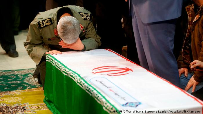 The coffin of General Soleimani with a Revolutionary Guard commander praying over it