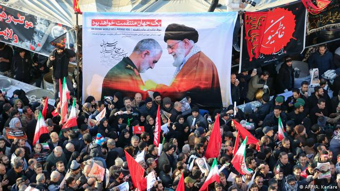 A picture of the Ayatollah and Soleimani held up by crowds (AFP/A. Kenare)