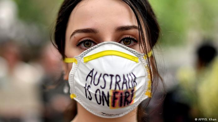 Una muchacha con una mascarilla que dice Australia is on fire.