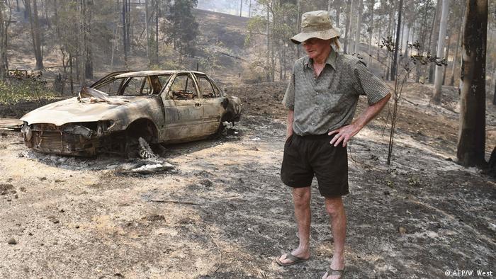 Pessoa ao lado de carcaça de carro queimado