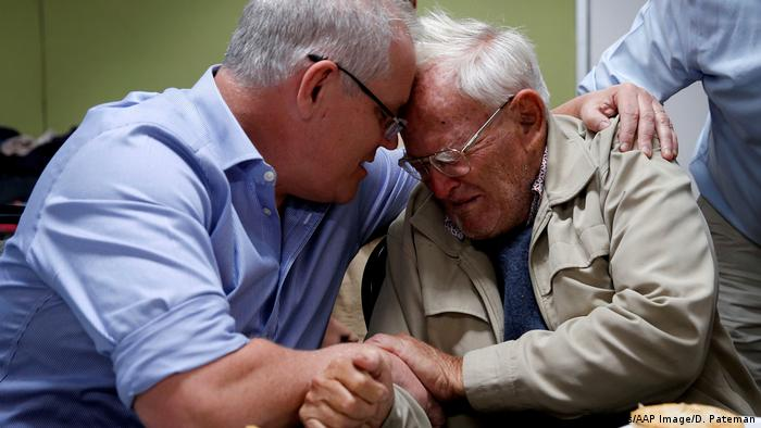 Scott Morrison comforts an old man.