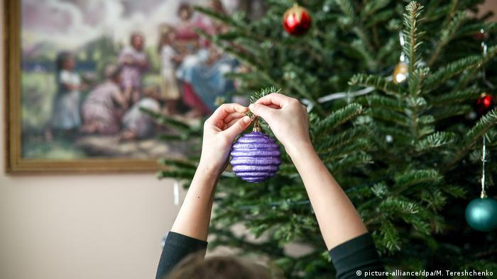 A decoration being hung on a tree