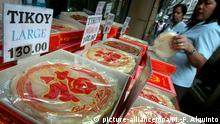 epa01244607 A Filipino bought a box of tikoy (Chinese sticky rice cake) along Ongpin China town Manila, Philippines, 04 February 2008. Filipino Chinese will celebrate Chinese New Year on 07 February 2008. Chinese tikoy is a popular gift and give aways during Chinese New Year. EPA/MIKE F. ALQUINTO |