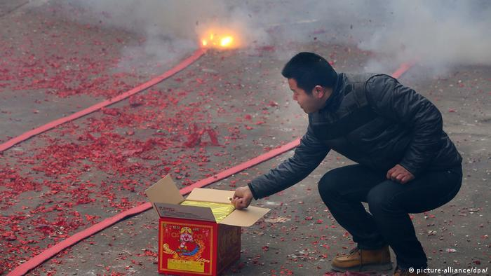 A man ignites fireworks on a street during Spring Festival (picture-alliance/dpa/)