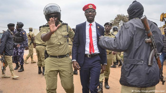 Ugandan singer-turned-politician Robert Kyagulanyi aka Bobi Wine is escorted by a police officer as he is arrested on charges of unlawful assembly before starting his first public meeting ahead of the presidential election next year on January 6, 2020