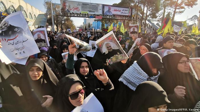Multidão de mulheres vestidas de preto com véu islâmico levantando retratos de Soleimani