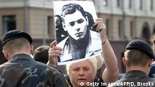Minsk, BELARUS: Olga Zavadskaya, mother of missing Dmitry Zavadsky, a cameraman in Minsk for Russian broadcaster ORT, holds his portrait durind the protest action in Minsk, 07 July 2005. Zavadsky disappeared on his way to pick up his collegue Pavel Cheremet from Minsk airport on July 7 2000. His car was later found empty. The journalists had become embroiled in tensions between Minsk and Moscow in 1997 after a report they made on illegal traffic at the Lithuanian border led to their arrests by the Belarussian KGB. AFP PHOTO/ DMITRY BRUSHKO. (Photo credit should read DMITRY BRUSHKO/AFP via Getty Images)