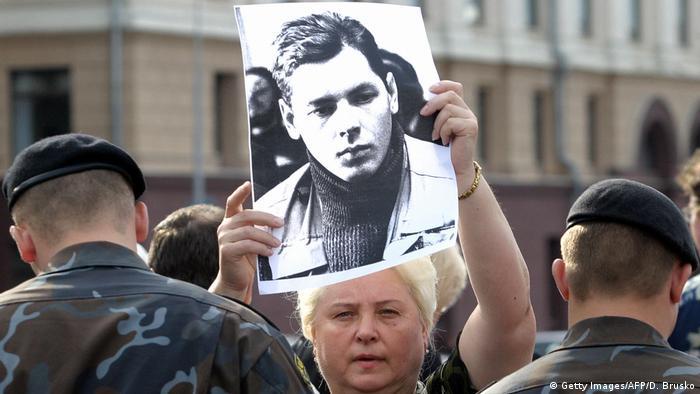 Женщина держит в руках портрет исчезнувшего оператора ОРТ Дмитрия Завадского