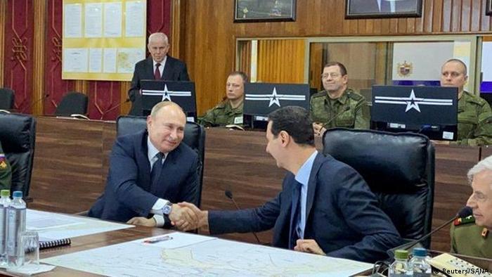 Russian President Vladimir Putin shakes hands with Syria's President Bashar al-Assad in Damascus