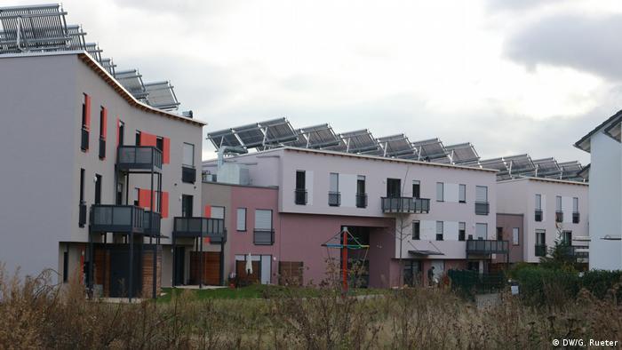 Wohnanlage in Frankfurt. Oben auf dem Dach sind solarthermische Kollektoren für Warmwasser und Heizung und Solarmodule (Panels), für die Stromerzeugung. Im Gebäude ist ein großer Wassertank, der die Wärme für die Heizungen und Heißwasser speichert. Mit Hilfe von einem zusätzlichen Wärmespeicher (Eisspeicher) im Garten und Wärmepumpen nutzt die Wohnanlage das ganze Jahr die Energie aus der Sonne und braucht kein Erdöl und Erdgas. In der Wohnanlage werden keine Zusatzkosten für Heizung erhoben. Ein Teil Wohnung sind besonders günstig (Sozialwohnungen)