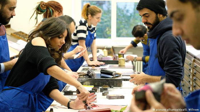 Refugees work at a graphic and bookbinding firm