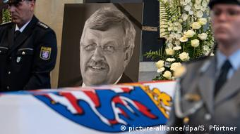 A photo of politician Walter Lübcke next to his casket which is decorated with flowers on one side