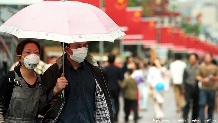 People cover their mouths during a SARS outbreak in China