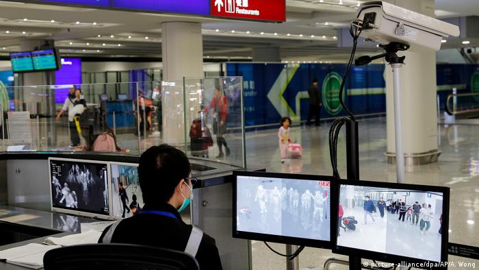 Chinese authorities screen travelers at an airport